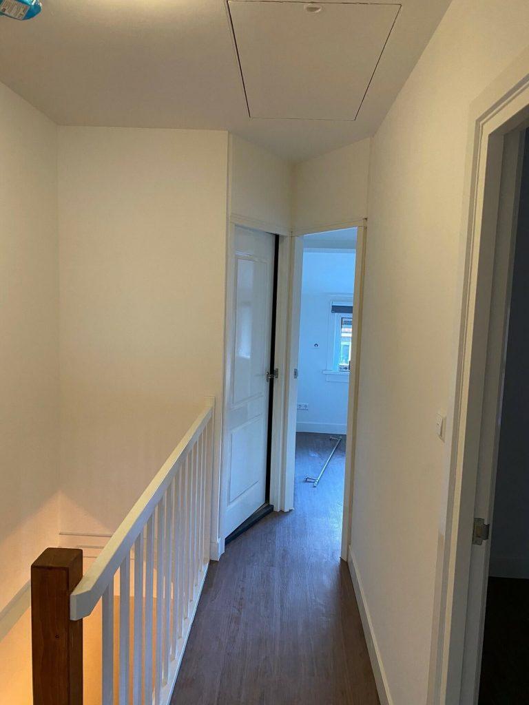 De overloop is het nieuwe trap hek te zien, er zijn op de gehele boven verdieping nieuwe deuren geplaatst. Ook hier loopt de PVC vloer door. In het plafond is het de nieuwe flisotrap te zien.